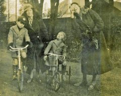 Mildred & Granny Elaine Hooke with her sons, George & John on bikes. Location unknown. Date approx. 1934.